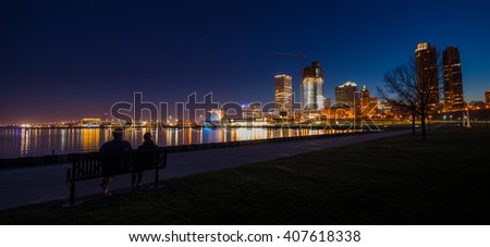 Couple sitting on a bench looking at City of Milwaukee Wisconsin at Night - stock photo
