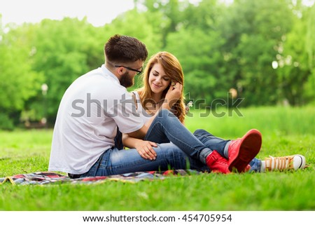 Couple sitting on a picnic blanket in a park. Guy gently placing flowers into girl's hair - stock photo