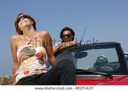 Couple sitting on a red carhood - stock photo
