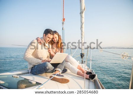 Couple sitting on a sailing boat looking at laptop computer - Beautiful woman and attractive man having fun on a boat while on vacation - stock photo