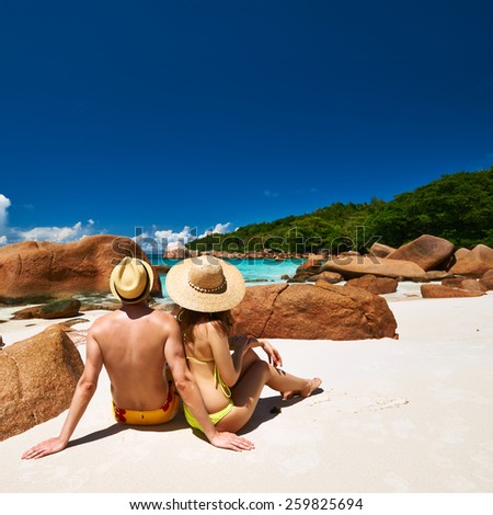 Couple sitting on a tropical beach at Seychelles - stock photo