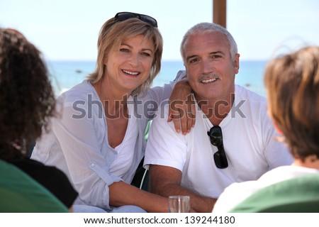 Couple sitting on bar terrace - stock photo