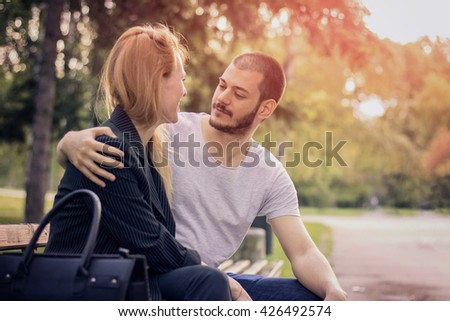 Couple sitting on bench at the park - stock photo