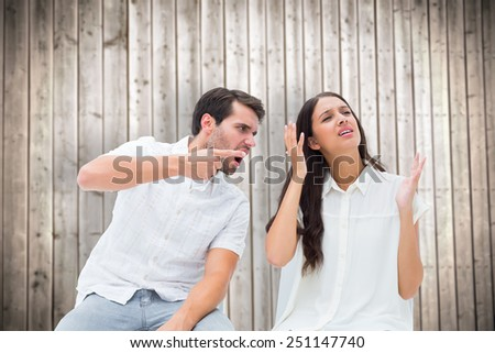 Couple sitting on chairs arguing against wooden planks background - stock photo