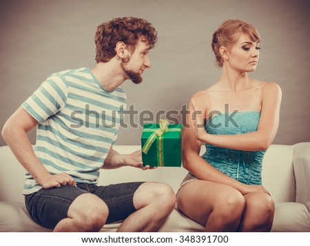 Couple sitting on couch at home. Young man giving offended woman gift box, girl refusing to accept present - stock photo