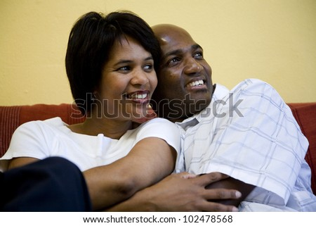 Couple sitting on couch smiling - stock photo
