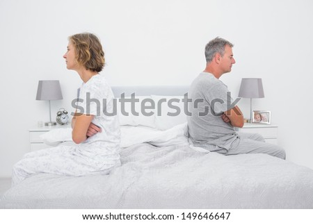 Couple sitting on different sides of bed not talking after dispute in bedroom at home