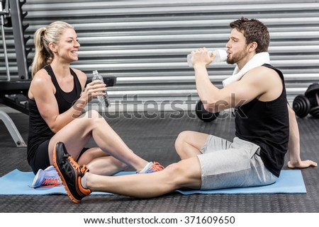 Couple sitting on fitness mat at crossfit gym - stock photo