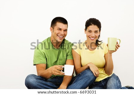Couple sitting on floor drinking coffee and smiling.