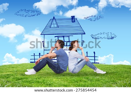 Couple sitting on floor together against blue sky over green field - stock photo