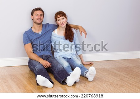 Couple sitting on floor together at home