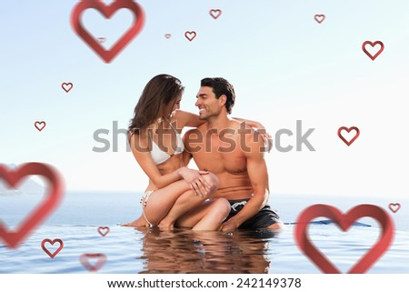 Couple sitting on pool edge together against hearts - stock photo