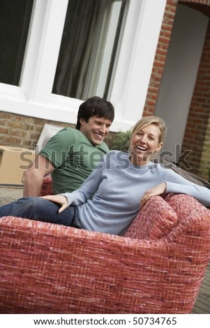 Couple sitting on sofa outside house - stock photo