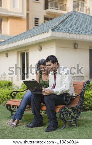 Couple sitting on the bench and using a laptop