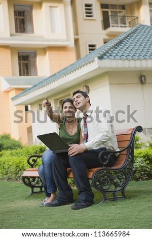Couple sitting on the bench with laptop and pointing - stock photo