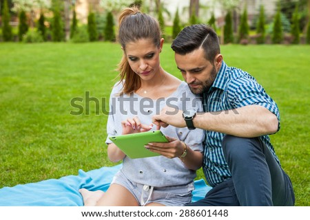 Couple sitting on the blanket in the garden, using tablet and smiling