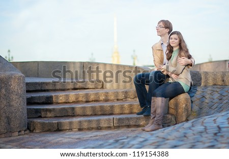 Couple sitting on the embankment with view to Peter and Paul Fortress in Saint-Petersburg - stock photo