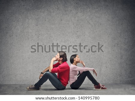 couple sitting on the floor thinking - stock photo