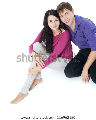 Couple sitting on the floor, white background - stock photo