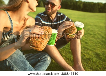 couple sitting on the grass in the park and eating sandwiches smiling - stock photo