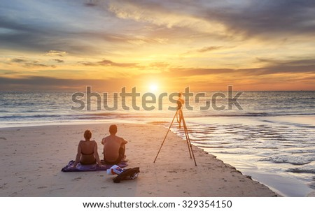 Couple sitting on the sunset beach, in Phuket Thailand - stock photo