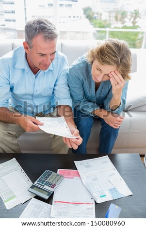 Couple sitting on their couch paying their bills at home in the living room - stock photo