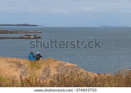 Couple sitting on top of a grassy knoll above an Icelandic fjord on Snaefellsnes peninsula - stock photo