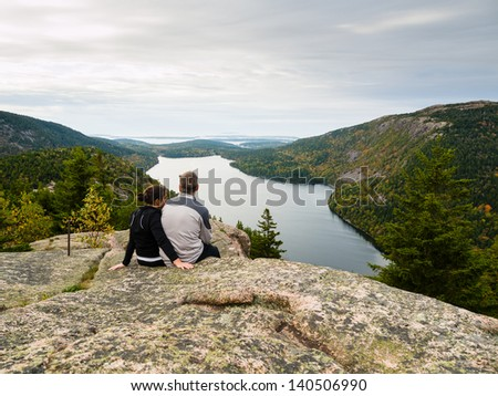 Couple sitting on top of a mountain over Jordan Pond lake in Acadia National Park - stock photo