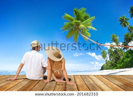 Couple Sitting on Wooden Floor at Beach - stock photo