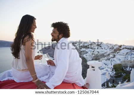 Couple sitting outdoors with champagne flutes and scenic background smiling