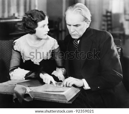 Couple sitting together and looking at a book with a worried facial expression