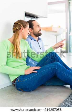 Couple sitting together on living room floor enjoying view