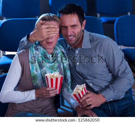 Couple sitting watching a movie in a cinema with containers of popcorn reacting in horror to something on screen