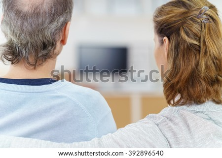 Couple sitting watching television at home with a view from behind between their heads