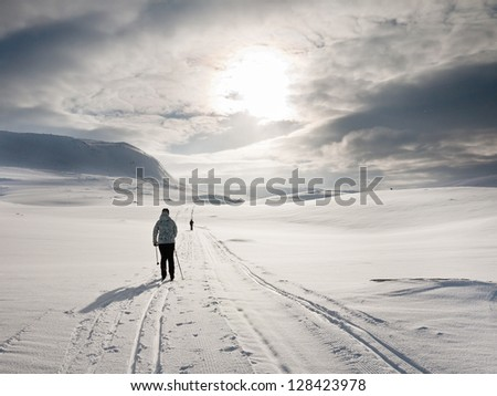 Couple skiing in a flat terrain towards the sun during an overcast day in the norwegian mountains at easter - stock photo