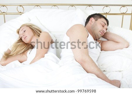 Couple sleeping back on back in bed - stock photo