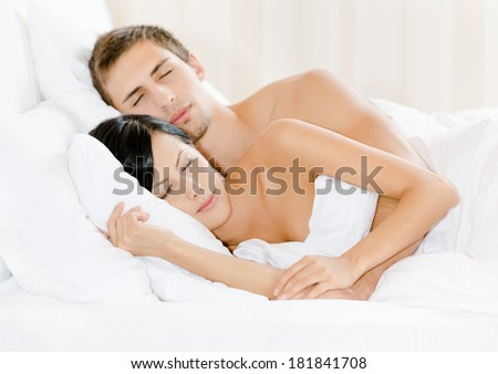 Couple sleeping in bed under white eiderdown - stock photo