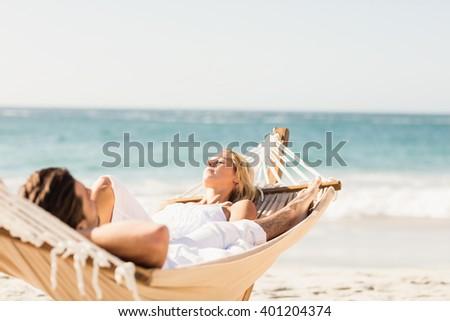 Couple sleeping in hammock on the beach - stock photo