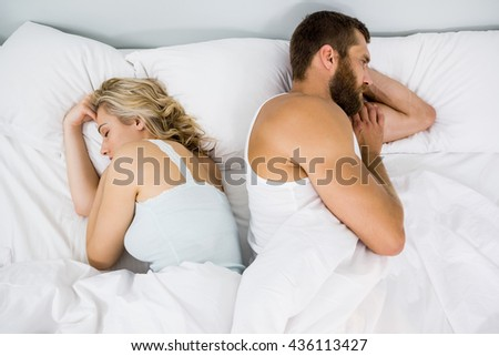 Couple sleeping on bed at bedroom