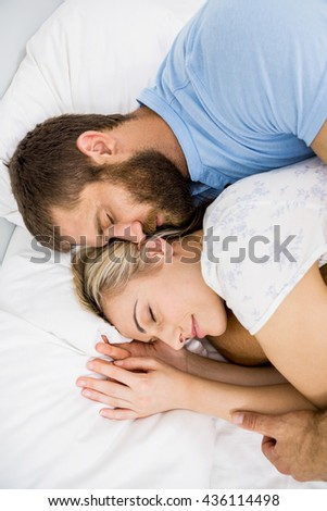 Couple sleeping on bed at bedroom - stock photo