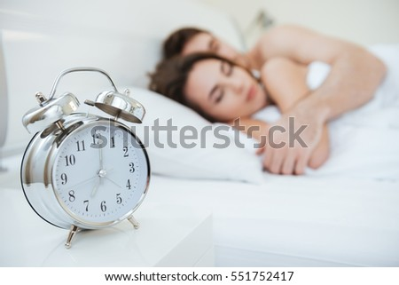 Couple sleeping on bed. Focus on clock which on nightstand near the bed