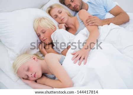 Couple sleeping with their cute children in bed - stock photo