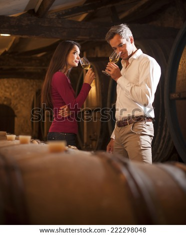 Couple smelling a glass of white wine in a traditional cellar surrounded by wooden barrels. - stock photo