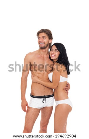 Couple smile wear swimsuit embrace looking side empty copy space, young man and woman tanned body swimwear isolated over white background - stock photo