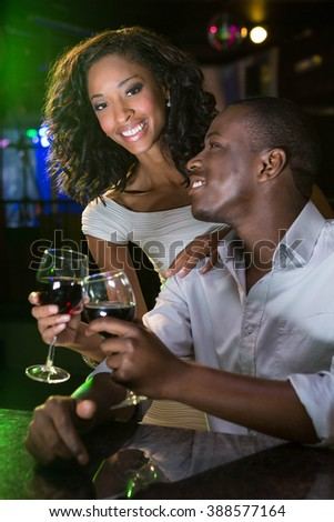 Couple smiling and toasting their wine glasses at bar counter in bar - stock photo