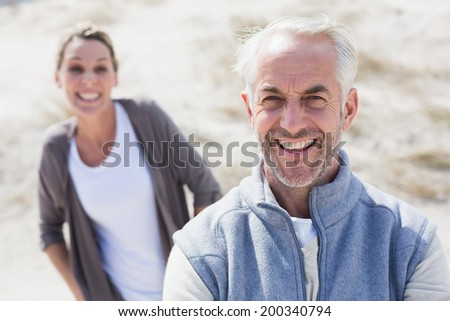Couple smiling at camera on the beach on a bright but cool day - stock photo