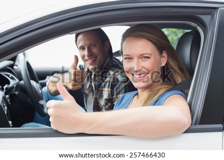 Couple smiling at the camera with thumbs up in their car - stock photo