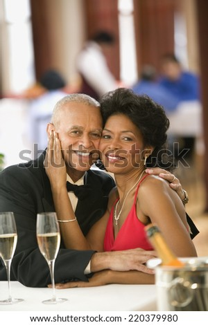 Couple smiling for the camera at dinner table - stock photo