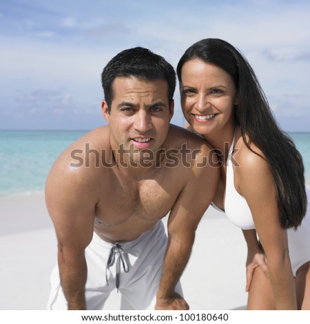 Couple smiling on the beach - stock photo