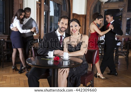 Couple Smiling While Enjoying Tango Performance In Restaurant